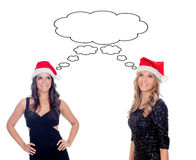 Two pretty girls with Christmas hat thinking Royalty Free Stock Photo