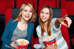 Two pretty girls in cinema Royalty Free Stock Photography
