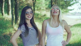 Two pretty girls with claret lips posing to camera in the park. 4k.  stock video footage