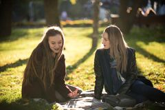 Two pretty girls in coats talking sitting on a plaid in autumn park stock photo