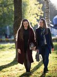 Two pretty girls in coats are walking in the autumn sunny park stock photo