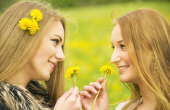 Two pretty girls with dandelions Royalty Free Stock Photos