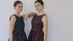 Two pretty girls demonstrate dresses from fashionable designer. He is famous for its intresting decisions of design and unusual prints. Clothes have same style stock video