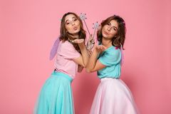 Two pretty girls dressed like fairies with wings. Holding magic wands while looking at camera over shoulder and blowing kiss isolated over pink background Royalty Free Stock Photography