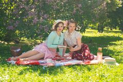 Two pretty girls friends sitting on the red blanket on the green grass and have summer picnic. happy woman having rest and fun on stock photography