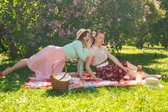 Two pretty girls friends sitting on the red blanket on the green grass and have summer picnic. happy woman having rest and fun on royalty free stock photo
