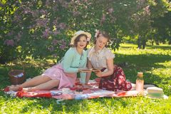 Two pretty girls friends sitting on the red blanket on the green grass and have summer picnic. happy woman having rest and fun on stock image