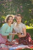 Two pretty girls friends sitting on the red blanket on the green grass and have summer picnic. happy woman having rest and fun on royalty free stock image