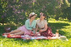 Two pretty girls friends sitting on the red blanket on the green grass and have summer picnic. happy woman having rest and fun on royalty free stock photography