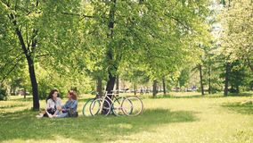 Two pretty girls friends are talking and laughing sitting on lawn in park on warn sunny day in summer. Modern bicycles. Two pretty cheerful girls best friends stock footage