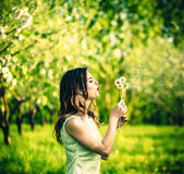 Two pretty girls in the garden blowing blowball flowers. Two pretty girls blowing blowball flowers in the garden Stock Image