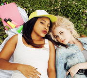 Two pretty girls on grass happy smiling, best friends having fun together, lifestyle people concept. Close up Stock Photos