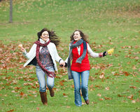 Two pretty girls having fun. In autumn park Stock Image