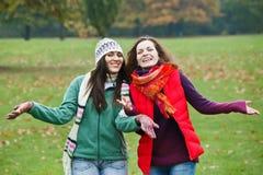 Two pretty girls having fun. In autumn park Royalty Free Stock Photo