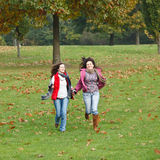Two pretty girls having fun. In autumn park Royalty Free Stock Images