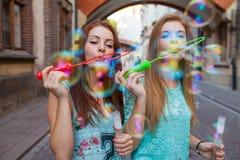 Two pretty girls having fun and blowing bubbles. Urban backgroun Stock Photos