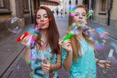 Two pretty girls having fun and blowing bubbles. Urban backgroun Stock Photography
