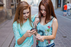 Two pretty girls holding smartphone and credit card. Urban backg Royalty Free Stock Photos