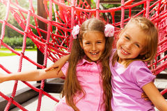 Two pretty girls hugging on rope of playground Stock Photo