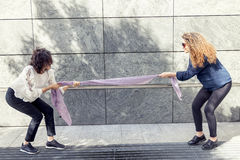 Two pretty girls improvise a tug of war with a scarf. For fun outdoor Royalty Free Stock Images