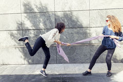 Two pretty girls improvise a tug of war with a scarf. For fun outdoor Royalty Free Stock Photography