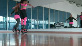 Two pretty girls in kangoo shoes jumping in front of the mirror stock footage