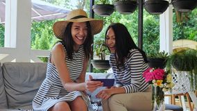 Two pretty girls are laughing during look over photos on phone sitting at cafe. Cheerful girls browsing smartphone together and smiling during sitting in the stock footage