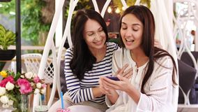 Two pretty girls are laughing during look over photos on phone sitting at cafe. Cheerful girls browsing smartphone together and smiling during sitting in the stock video footage