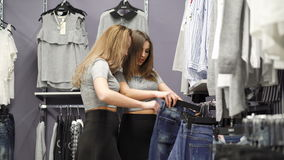 Two pretty girls looking on the trousers in the fashionable boutique 4K stock video