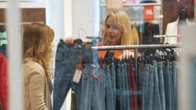 Two pretty girls looking on the trousers in the fashionable boutique 4K stock footage
