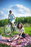 Two pretty girls make a picnic on field Royalty Free Stock Images