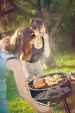 Two pretty girls making food on grill Stock Photos