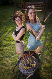 Two pretty girls making food on grill Stock Photography