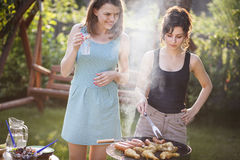 Two pretty girls making food on grill Royalty Free Stock Photos