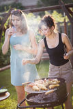 Two pretty girls making food on grill Royalty Free Stock Photo