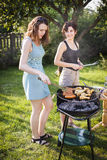 Two pretty girls making food on grill Royalty Free Stock Image