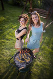 Two pretty girls making food on grill Royalty Free Stock Images
