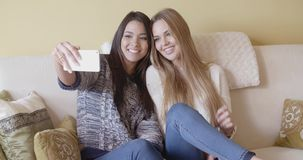Two pretty girls posing for a selfie. Two pretty girls sitting together on a sofa in the living room posing for a selfie on a mobile phone smiling and laughing stock footage