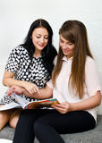 Two pretty girls reading magazine Royalty Free Stock Photos