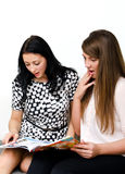Two pretty girls reading magazine Royalty Free Stock Images