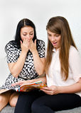 Two pretty girls reading magazine Stock Photo