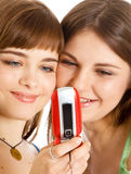 Two pretty girls reading SMS on mobile phone. Isolated on white background Royalty Free Stock Image