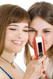 Two pretty girls reading SMS on mobile phone Royalty Free Stock Photography