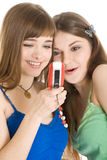 Two Pretty Girls Reading SMS On Mobile Phone Stock Photos