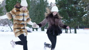 Two pretty girls running through the snow in park. Slowly.  stock footage