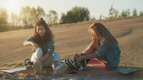 Two pretty girls with sandboard in Dubai desert at sunset. Summer vacation, travel lifestyle and tourism. Beautiful