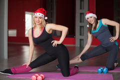Two pretty girls in santa claus hats exercise on mats in fitness. Two pretty girls in santa claus hats do stretching, exercises for hips on mats in sports hall Royalty Free Stock Image