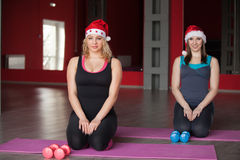 Two pretty girls in santa claus hats sit on mats in fitness cent Royalty Free Stock Image