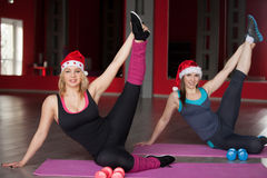 Two pretty girls in santa claus hats stretching legs on mats in Stock Photo