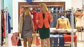 Two pretty girls with shopping, satisfied, leave the store. stock video footage